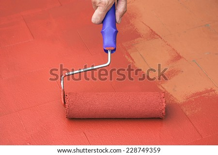 Hand painting a red floor with a paint roller for waterproofing - stock photo