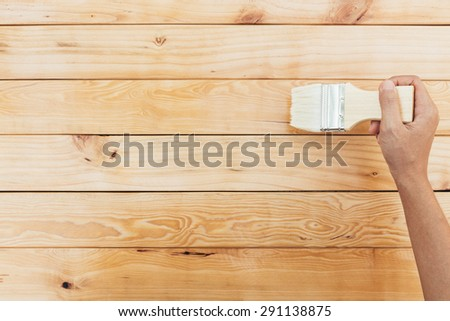 hand painting brush clear lacquer on wood surface - stock photo