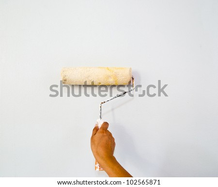 Hand painting the wall with roller - stock photo