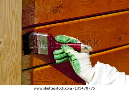 hand painting wooden wall with a paintbrush  in orange outdoor shot - stock photo