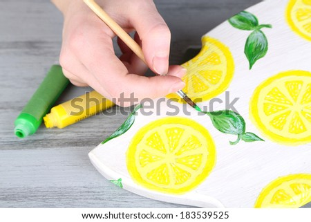 Hand paints on hand made cutting board and art materials - stock photo