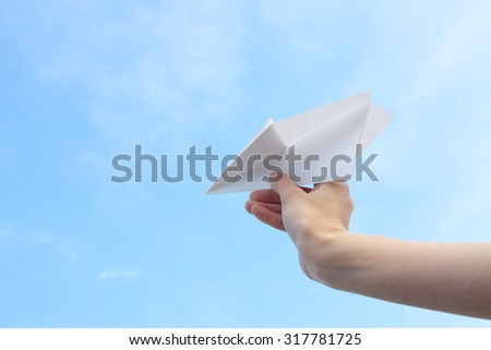 Hand, paper airplane - stock photo