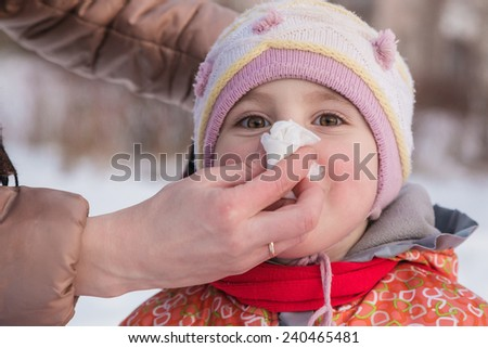 Hand parent helping her child to blow his nose. - stock photo