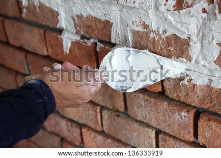 hand pastering cement mortal on the brick wall - stock photo