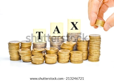 hand paying tax - a pile of coins with the word tax - stock photo