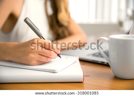 Hand pen coffee cup laptop table close up bokeh background taking notes