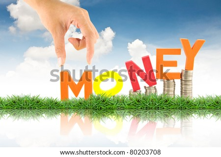 Hand pick up money word, against blue sky background - stock photo