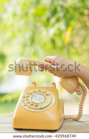 hand pick up old day phone or rotary telephone on wood table - stock photo