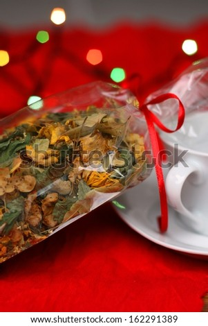 Hand picked natural herbal tea in a gift bag, tea cup and christmas lights in background, shallow DOF - stock photo