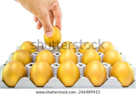 Hand picking a golden egg  - stock photo