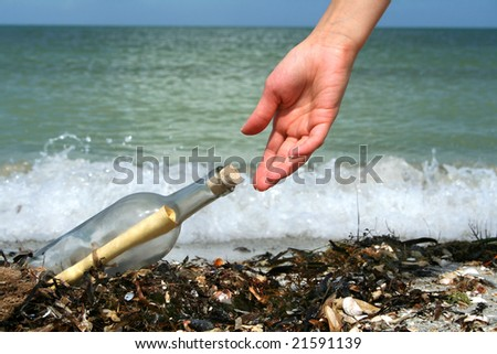 Hand picking a message in a bottle  washed ashore. - stock photo