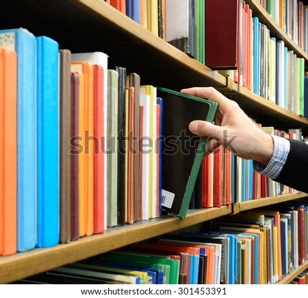 Hand picking book in library bookshelf - stock photo