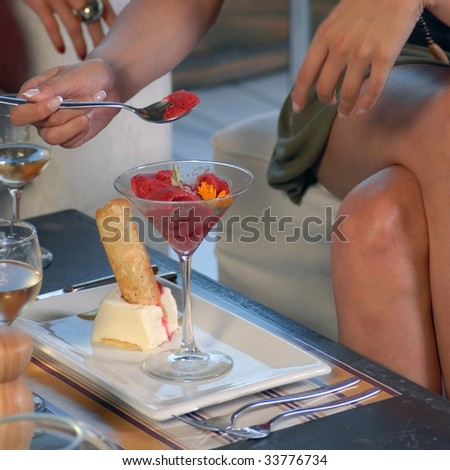 hand picking strawberry ice cream in glass cup