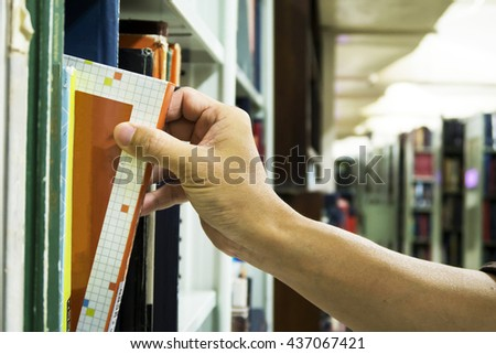 Hand picking up a book from the library shelf - stock photo
