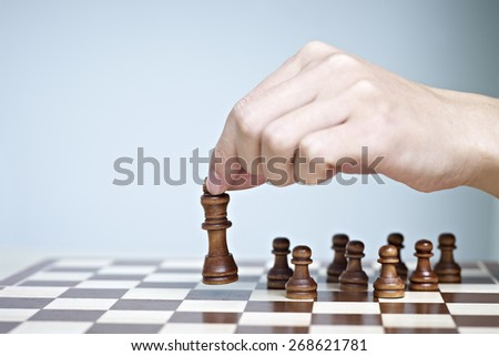 hand picking up and moving a chess piece. - stock photo
