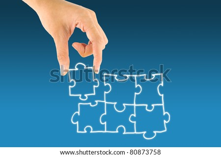 Hand picking up jigsaw icon touch screen - stock photo