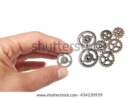 Hand placing a gear together with others, isolated on white                                - stock photo