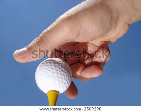 Hand placing a golf ball on a tee - stock photo