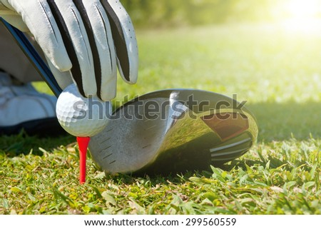 Hand placing a golf ball on a tee, next to a club. - stock photo
