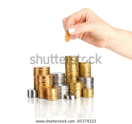 Hand placing coin on stack of coins - stock photo