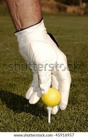 Hand placing golf ball on a tee - stock photo