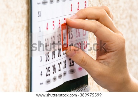 hand placing red mark on calendar date
