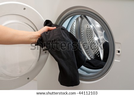 Hand placing the clothes in the drum of washing machine
