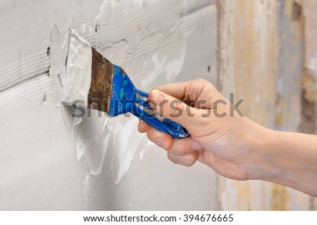 hand plastering a wall - stock photo