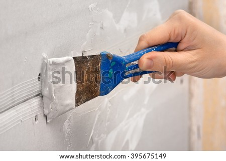 hand plastering a wall with spatula, closeup - stock photo
