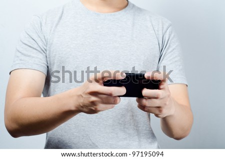 Hand play game on mobile phone - stock photo