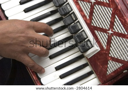 hand play the accordion in the streets of bruges - stock photo