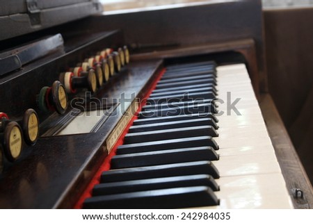 Hand play vintage old piano ,wooden with red line and sound button piano key background, Children's fingers on the keys of a piano playing/Etude ,keyboard ,music and song instrument.