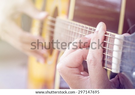 Hand playing acoustic guitar, color filter. - stock photo