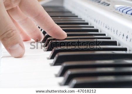 hand playing music on the piano - stock photo