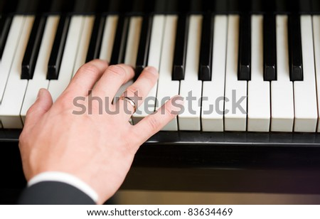 Hand playing music on the piano, hand and piano player - stock photo