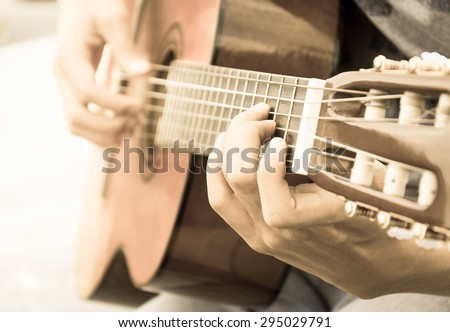hand playing on acoustic guitar - soft focus with vintage filter