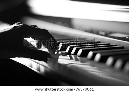 Hand playing on digital piano. Close-up. Small depth of field. Black and white. - stock photo