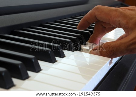 Hand playing on the piano - stock photo