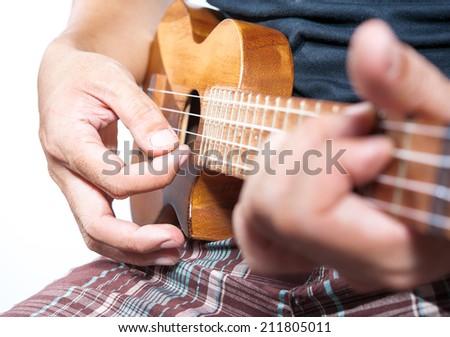 Hand playing ukulele, small string instrument - stock photo