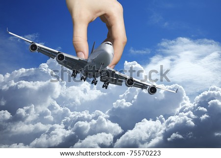 Hand playing with a real jet aircraft - stock photo