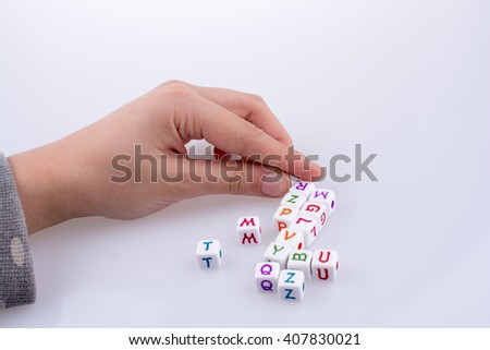 Hand playing with Letter cubes on a white background