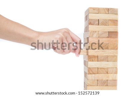 Hand playing with the wood game (jenga). on white background. - stock photo
