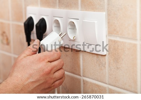 Hand plugging power cord into a wall outlet - closeup - stock photo