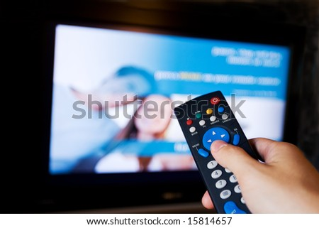 Hand pointing a tv remote control towards the television. - stock photo