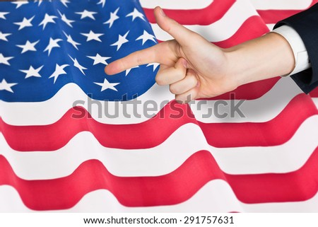 Hand pointing against rippled us flag