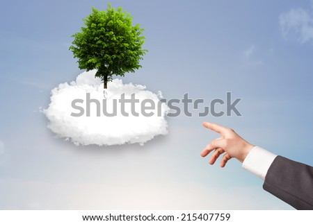 Hand pointing at a green tree on top of a white cloud concept - stock photo