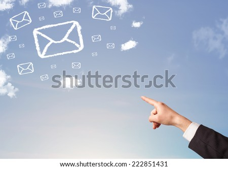 Hand pointing at mail symbol and icon clouds on blue sky - stock photo