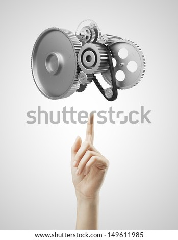 hand pointing at metal gears and cogs wheels - stock photo