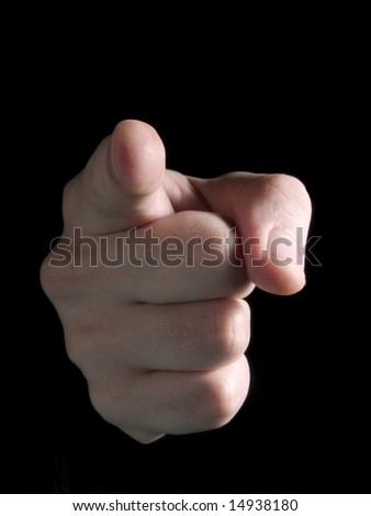 Hand pointing at observer isolated on black. - stock photo