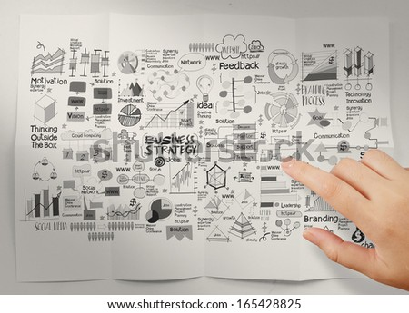 hand pointing  business strategy on crumpled paper background as concept - stock photo